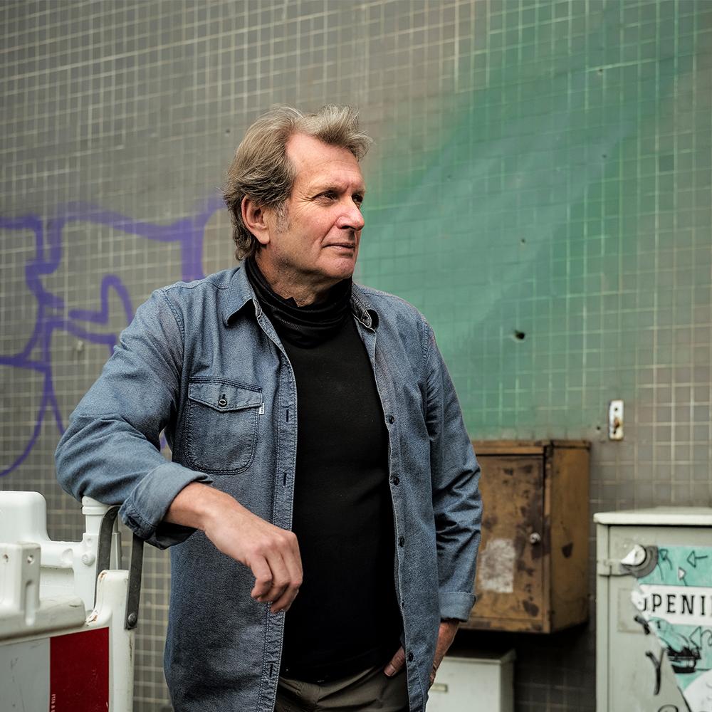 Gerhard Trabert steht an einem Baustellenzaun und blickt zur Seite.