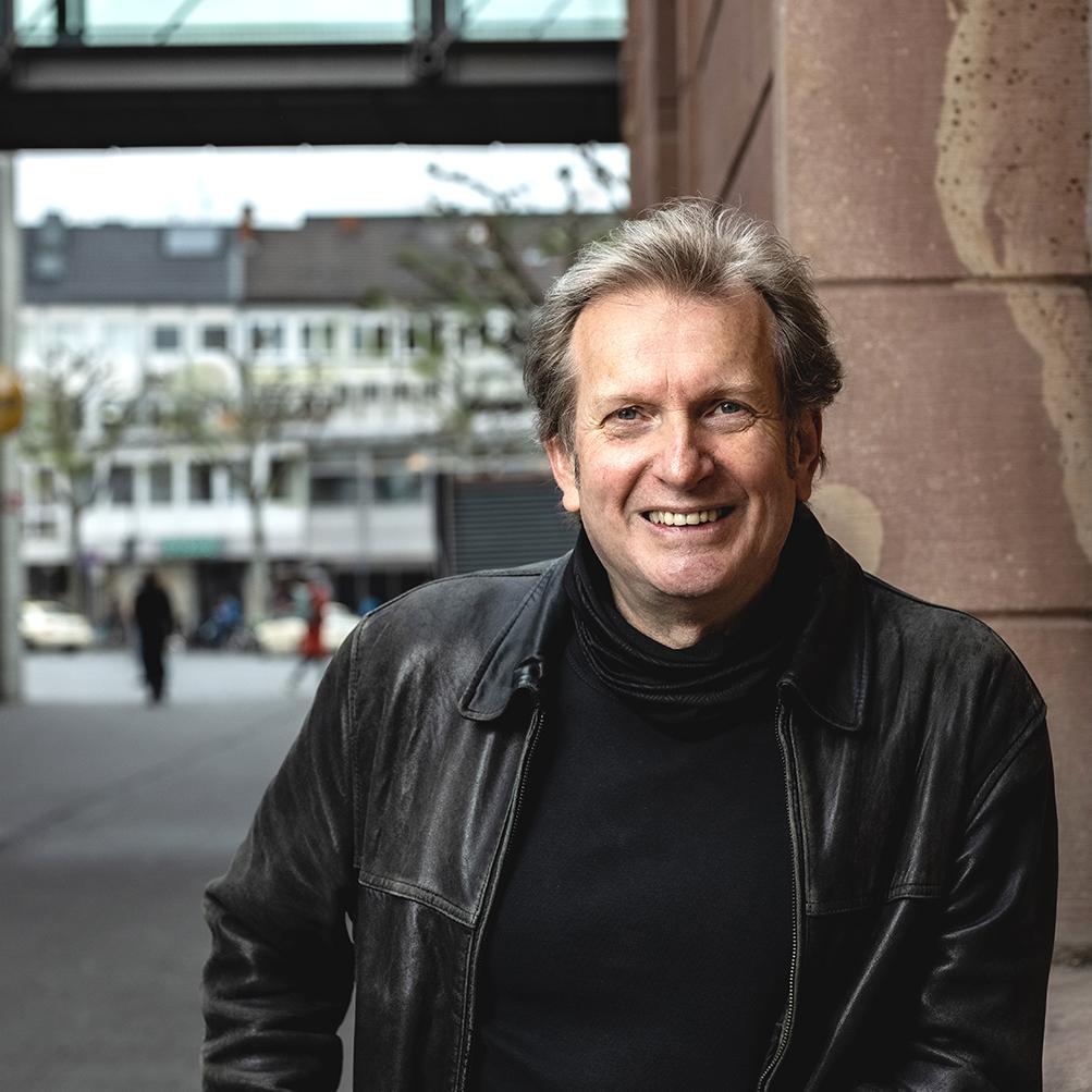 Prof. Dr. Gerhard Trabert lehnt an einer Wand in der Mainzer Fußgängerzone und schaut lachend in die Kamera.