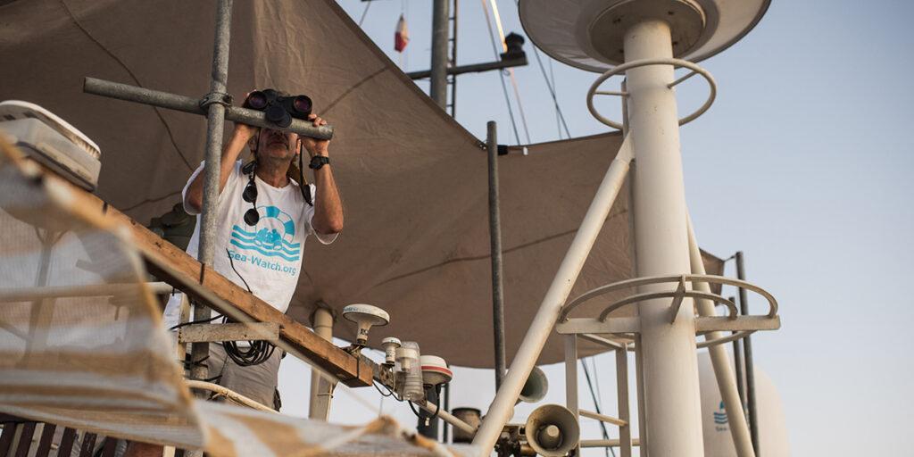 Flucht und Migration: Prof. Dr. Gerhard Trabert schaut durch ein Fernglas von der Sea Watch aufs Mittelmeer.