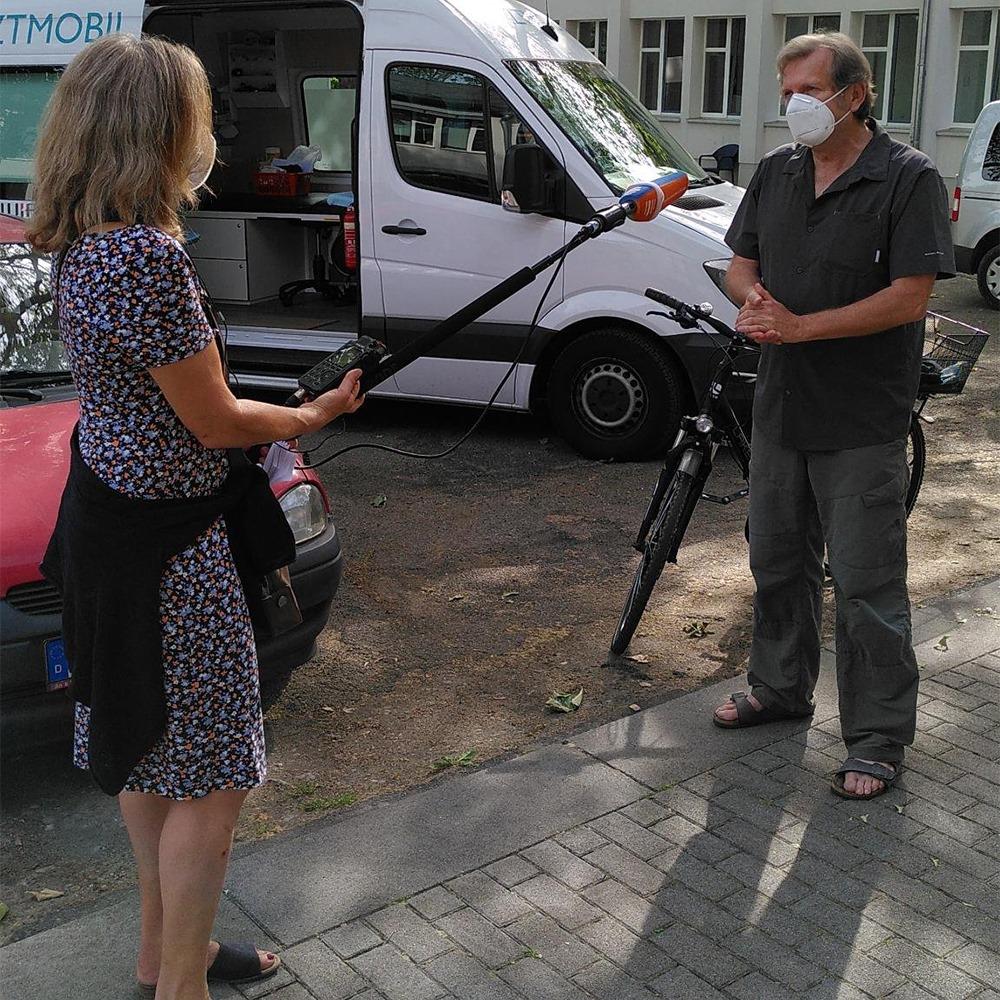 Prof. Dr. Trabert steht beim Interview mit dem Deutschlandfunk vor dem Arztmobil.