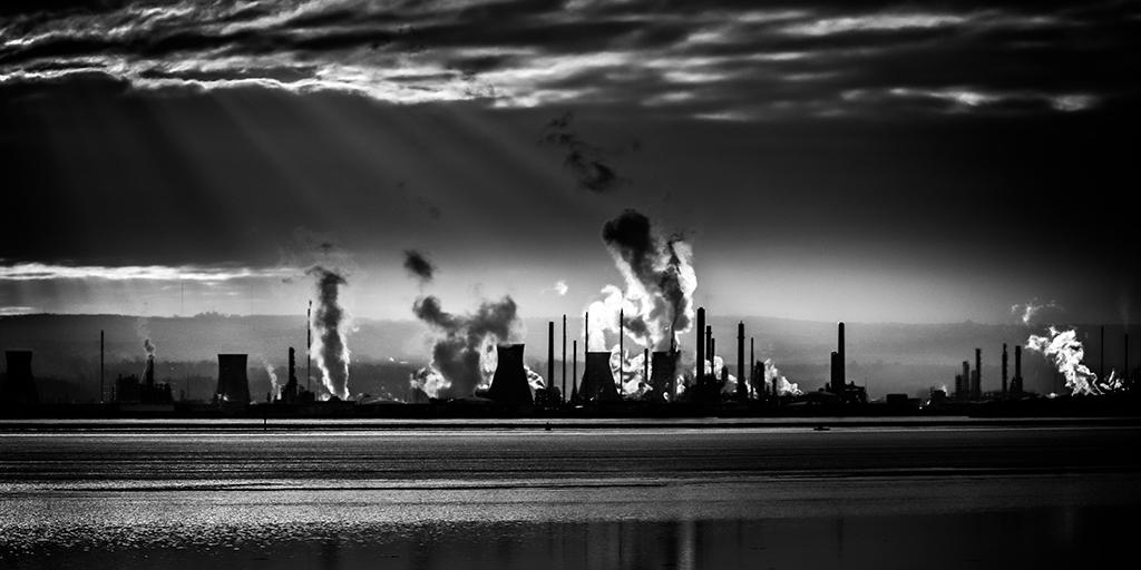 Solidarität und soziale Gerechtigkeit: Schwarz-Weiß-Foto von einem Industriegebiet mit rauchenden Schornsteinen.