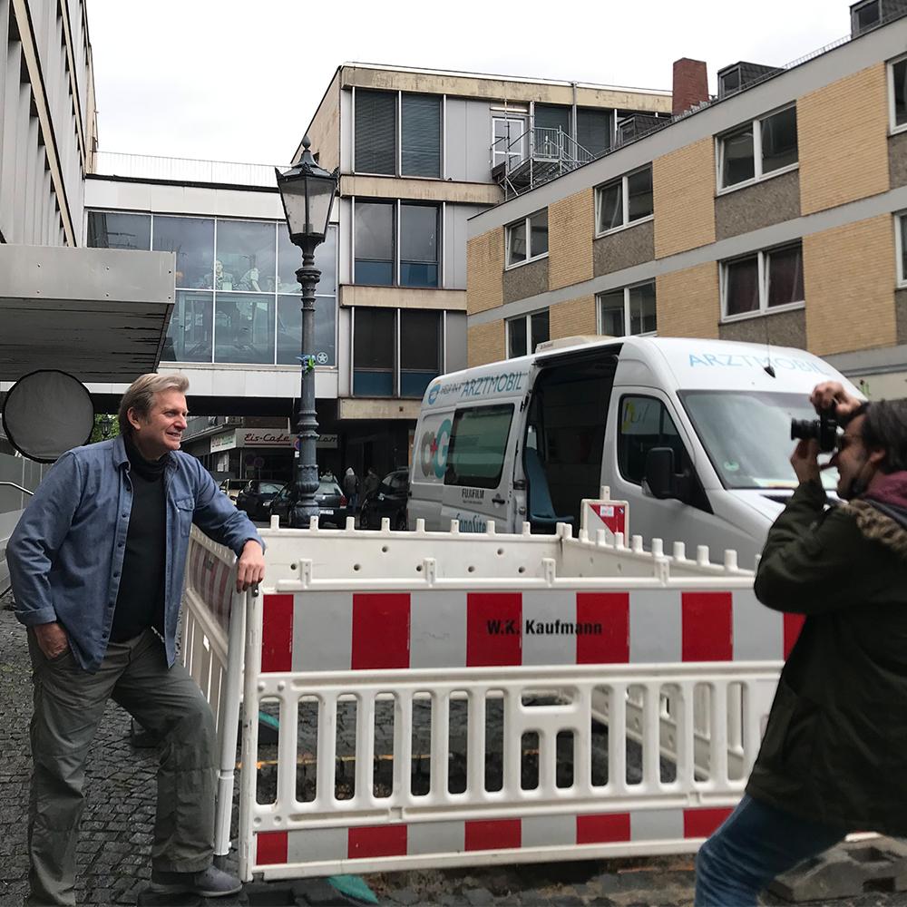 Plakat-Fotoschooting in Mainz mit Prof. Dr. Gerhard Trabert im Bild angelehnt an einen Bauzaun.