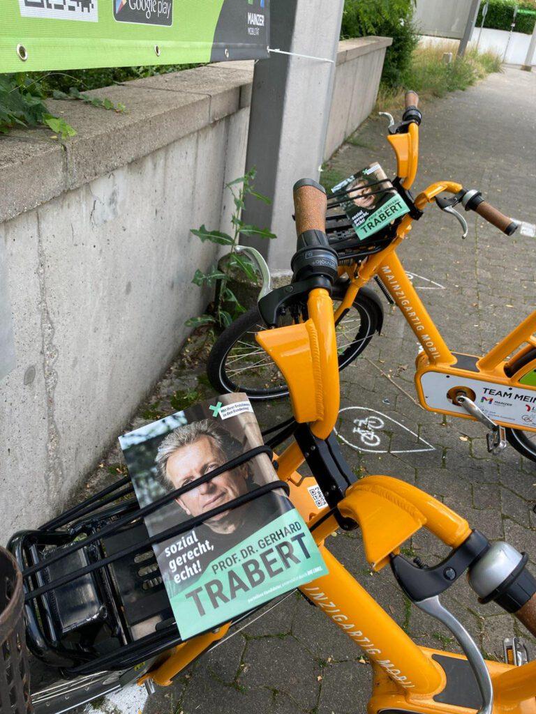 Team Trabert: Zwei gelb-orange Leihfahrräder vor einer Mauer mit Trabert-Flyern auf dem Gepäckständer.
